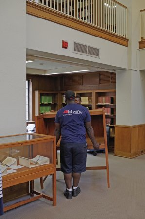 Movers relocate a study carrel.