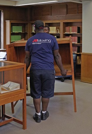 Movers relocate furniture in the Morse Reading Room.